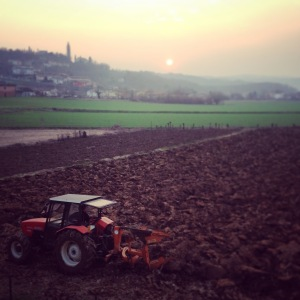 The sun sets on day 100 of our countdown. A farmer turns the soil on his tractor. Pianezze in the distance.