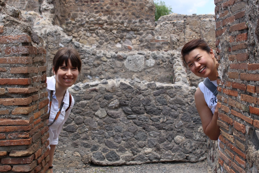 two modern day citizens of Pompeii peek from behind the ruins