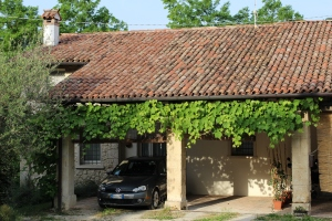 La Colombara from the courtyard. Cascading grapevines and an ancient farmhouse.