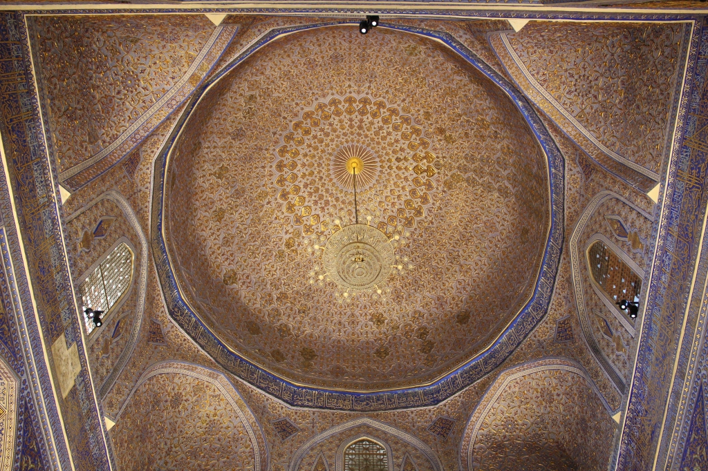 ornately decorated gold leaf interior of the blue dome from within the chamber above Timur's crypt