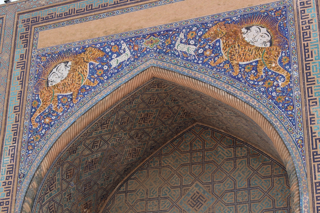 detail of the mystical tiger-lion beasts above the entrance facade of the Sher-Dor Madrasah as viewed from Registan Square
